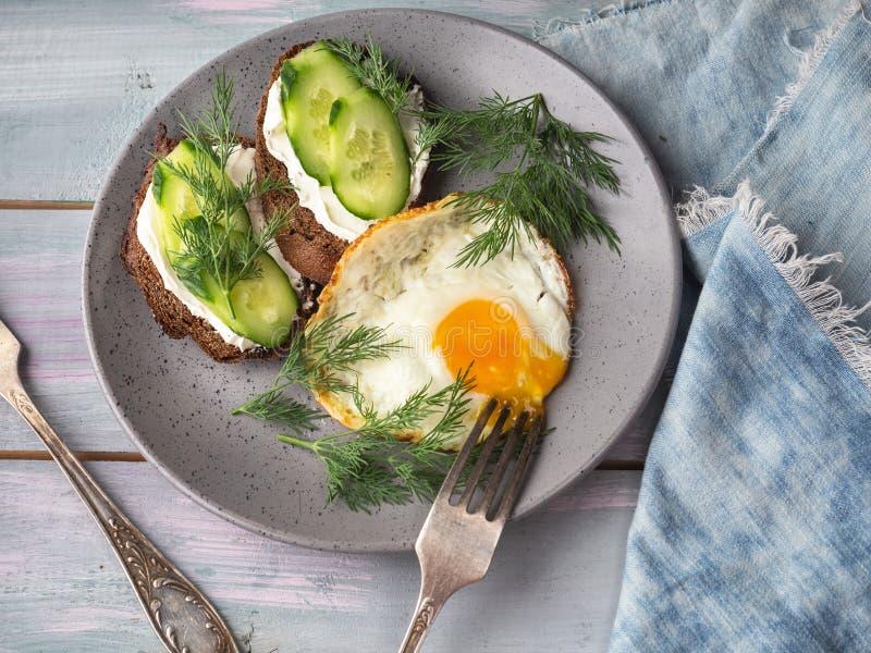 Kesosmörgåsar och nya gurkaskivor och förvanskade ägg på en grå platta för en ljust frukost och bestick och a arkivbild