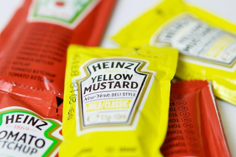 A ketchup e a mostarda de Heinz marcam em uns saquinhos fotos de stock
