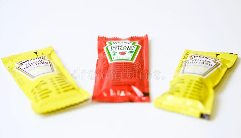 A ketchup e a mostarda de Heinz marcam em uns saquinhos fotografia de stock