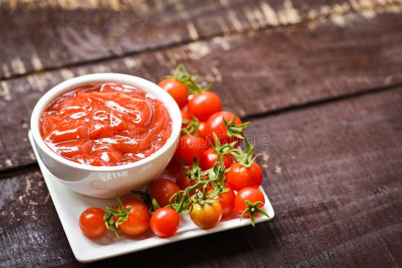 Ketchup en tasse et tomates fraîches sur la fin blanche de plat vers le haut de la sauce tomate sur le fond foncé en bois photo libre de droits