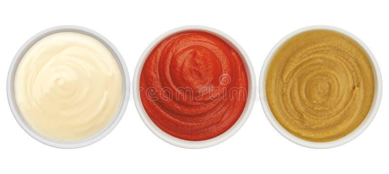 Ketchup, maionese e senape isolati sulla vista superiore del fondo bianco fotografie stock