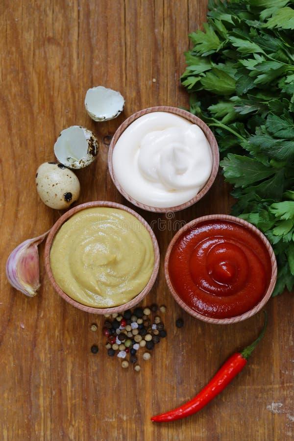 Ketchup, mayonaise en mosterd - drie soorten saus royalty-vrije stock afbeeldingen