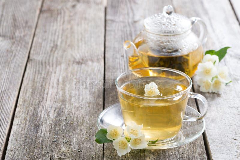 Ketel en een kop van groene thee met jasmijn op houten achtergrond royalty-vrije stock afbeeldingen