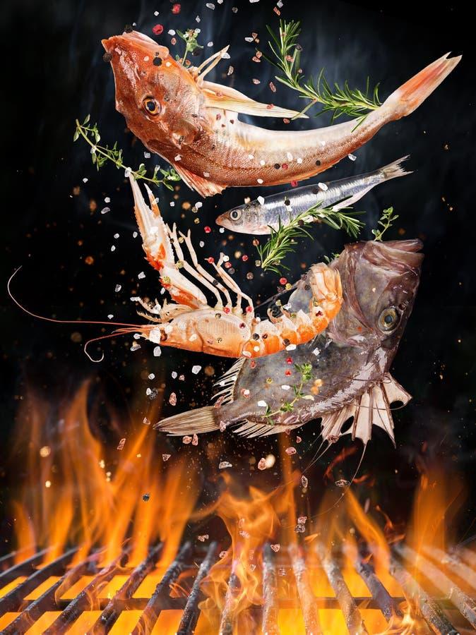 Ketelgrill met brandvlammen, gietijzerrooster en smakelijke zeevissen die in de lucht vliegen stock foto's