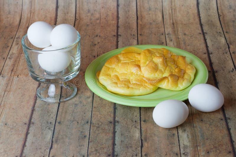 Keto怂恿在木板条板的面包与一碗鸡蛋 图库摄影