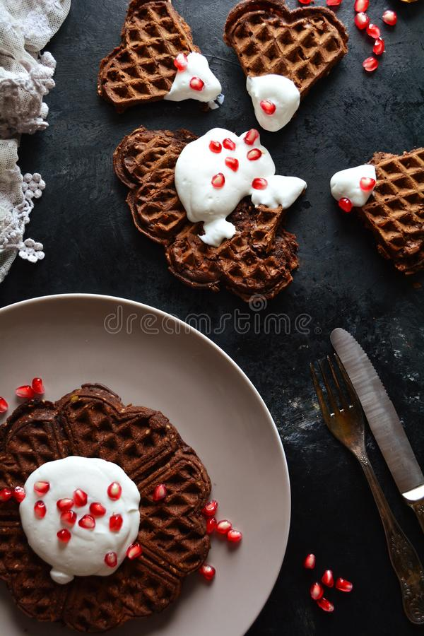 Keto Chocolate Waffles with Whipped Cream and Pomegranate Seeds. Homemade ketogenic diet waffles with whipped cream and pomegranate seeds on black background stock photos