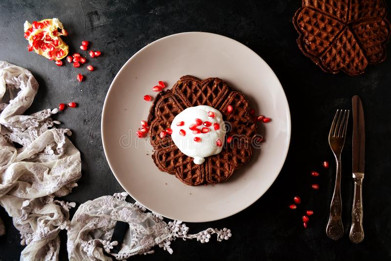 Keto Chocolate Waffles with Whipped Cream and Pomegranate Seeds. Homemade ketogenic diet waffles with whipped cream and pomegranate seeds on black background royalty free stock photos