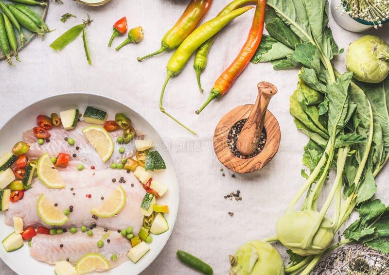 Keto dieetvisschotel met groenten in witte pan op de lichte achtergrond van de keukenlijst met ingrediënten en mes, hoogste menin royalty-vrije stock fotografie