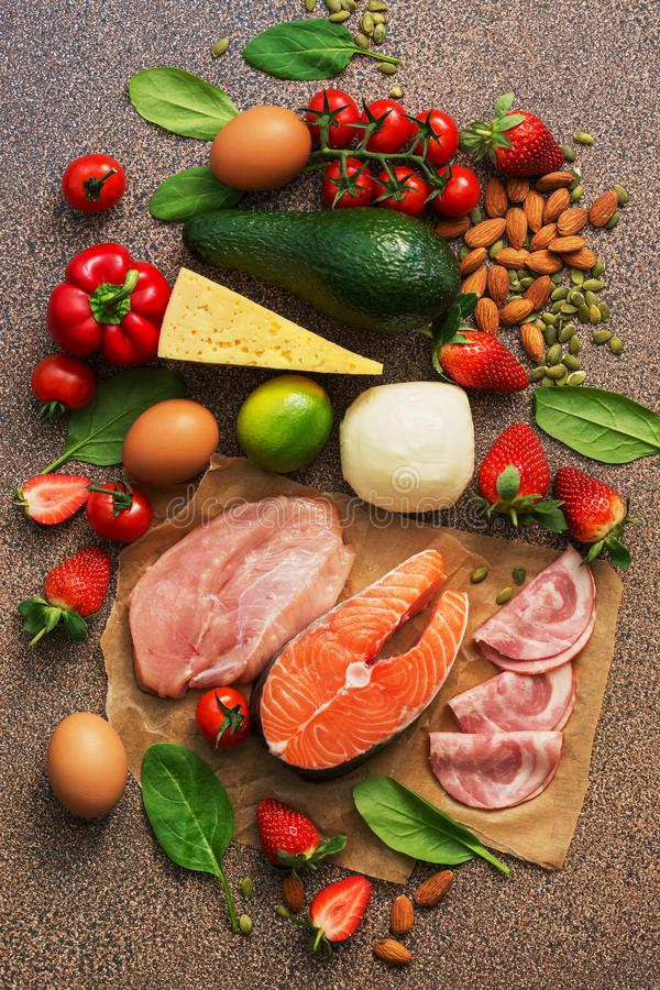 Keto diet concept.Healthy foods low in carbohydrates. Salmon, chicken, vegetables, strawberries, nuts, eggs and tomatoes, cutting. Board. Top view royalty free stock image