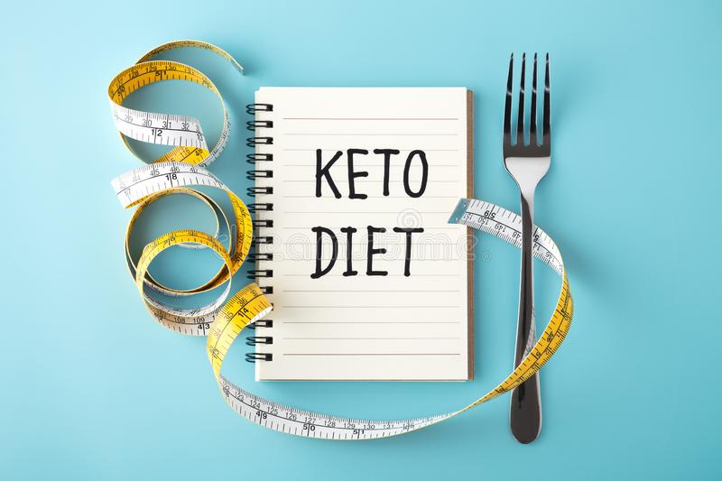 Keto diet concept on blue background. Keto diet word on notebook with measuring tape and fork on blue background stock images