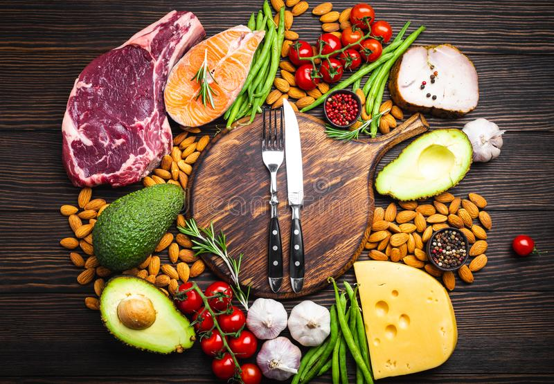 Keto diet foods. Knife and fork over wooden cutting board and ketogenic low carbs ingredients for healthy eating concept and weight loss, top view. Keto foods stock photography