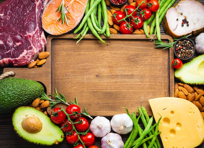 Keto diet foods. Wooden cutting board and ketogenic low carbs ingredients for healthy weight loss diet, top view, copy space. Keto foods: meat, fish, avocado stock photos