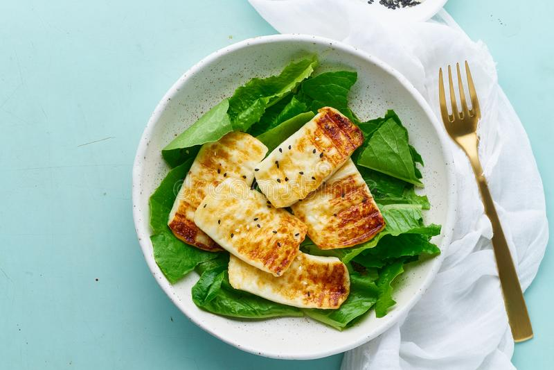 Keto ketogenic diet haloumi with lettuce on pastel background closeup. Keto ketogenic diet grilled haloumi with lettuce, mediterranean cuisine on pastel stock image