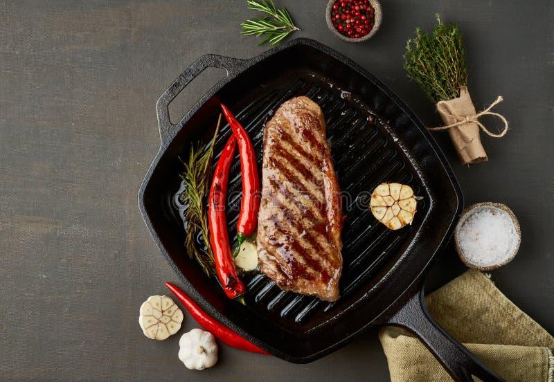 Keto ketogenic diet medium beef steak, fried striploin on grill pan. Paleo food recipe with meat, seasoning royalty free stock images