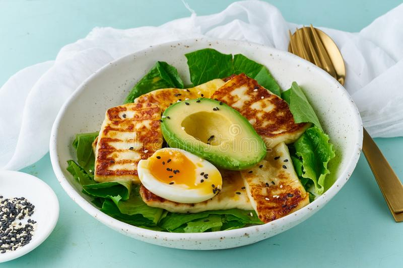 Keto ketogenic diet soft boiled eggs with avocado and lettuce on pastel background closeup. Keto ketogenic diet soft boiled eggs with grilled haloumi, avocado royalty free stock image