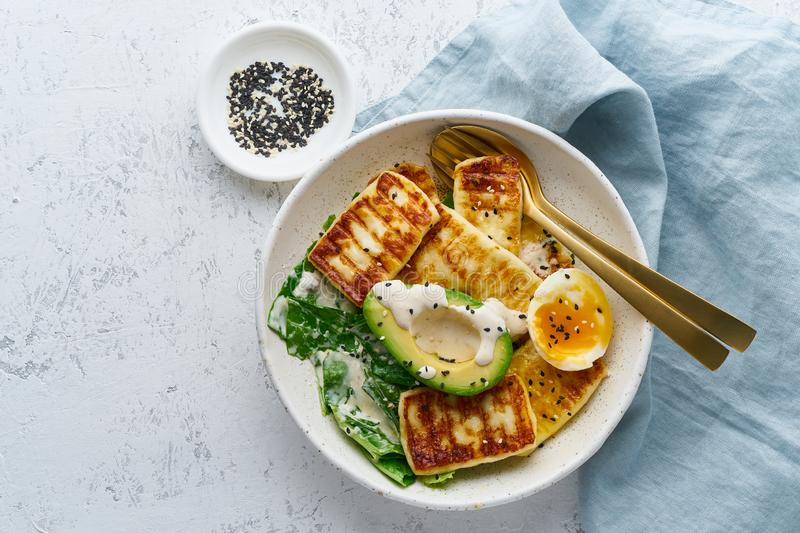 Keto ketogenic diet soft boiled eggs with avocado and lettuce on pastel background top view copy space. Keto ketogenic diet soft boiled eggs with grilled haloumi stock images