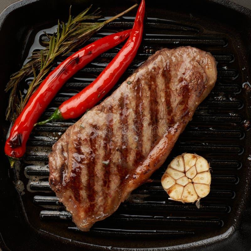Keto ketogenic diet medium beef steak, fried striploin on grill pan. Paleo food recipe with meat, seasoning royalty free stock image