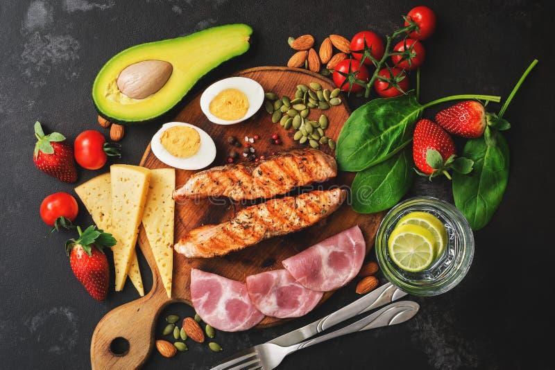 Keto, ketogenic dieta, niska węglowodanowa zawartość Piec na grillu łosoś, warzywa, truskawki, ser, baleron i woda z cytryną, cze obraz stock