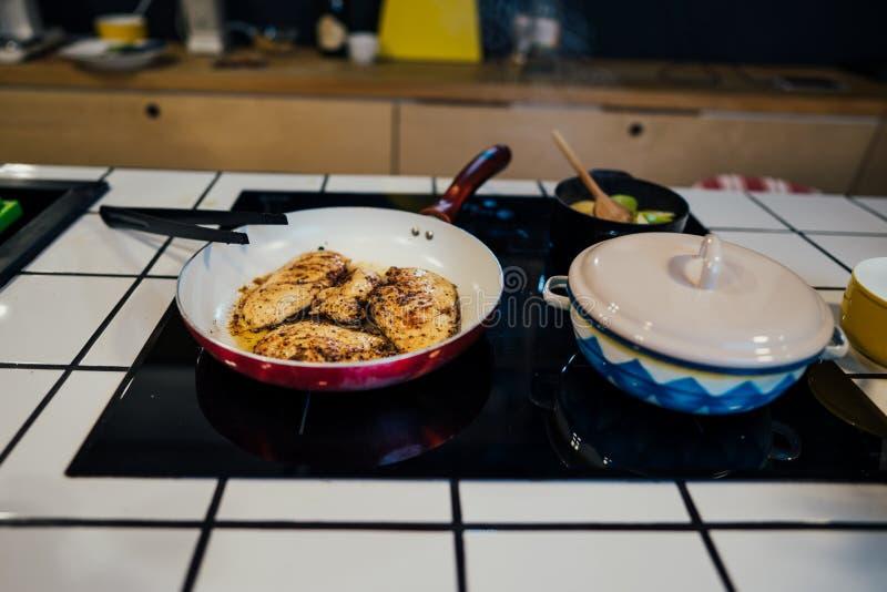 Keto maaltijd op inductiehaardplaat wordt, healty die het op dieet zijn concept, kippenborst met olijfolie wordt voorbereid voorb stock afbeeldingen