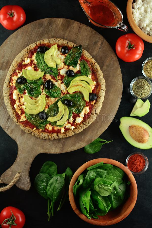 Keto Pizza with Sugar Free Tomato Paste, Crumbled Cheese, Spinach, Avocado and Olives. A set of photos showing low-carb, sugar-free keto diet pizza with keto royalty free stock image
