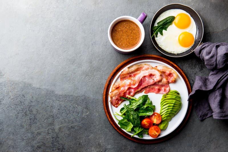 Ketogenic dieetontbijt braadde ei, bacon en avocado, spinazie en kogelvrije koffie Lage hoge carburator - vet ontbijt stock fotografie