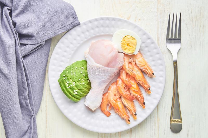 Ketogenic diet concept. A set of products for low carb keto diet. Green avocado, sesame, chicken leg, eggs and shrimps. Healthy royalty free stock photos