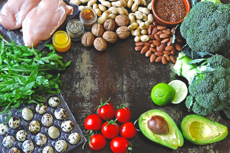 Ketogenic diet concept. A set of products of the low carb keto diet. Green vegetables, nuts, chicken fillet, flax seeds, quail egg royalty free stock photography