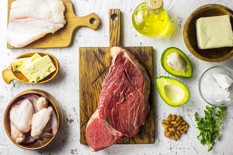 Ketogenic diet food. Balanced low-carb food background. Fish, meat, cheese, nuts on a white background. Healthy balanced food with royalty free stock photos