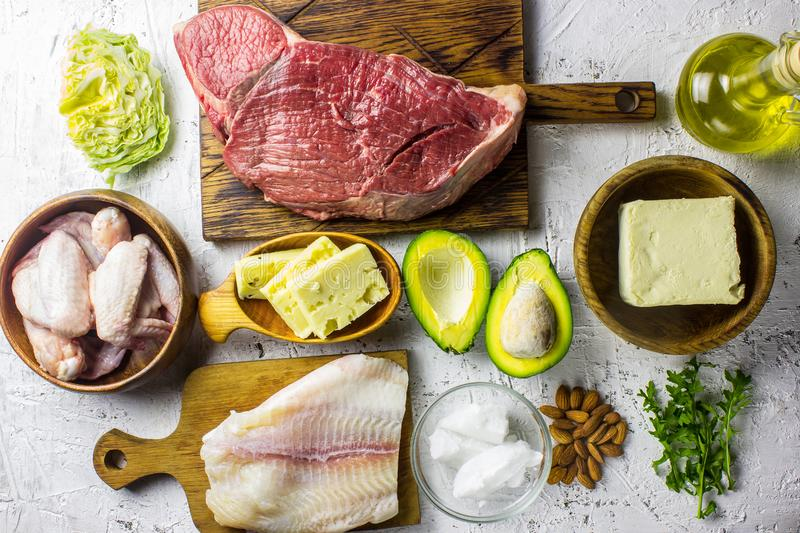 Ketogenic diet food. Balanced low-carb food background. Fish, meat, cheese, nuts on a white background. Healthy balanced food with. High content of healthy fats royalty free stock photos