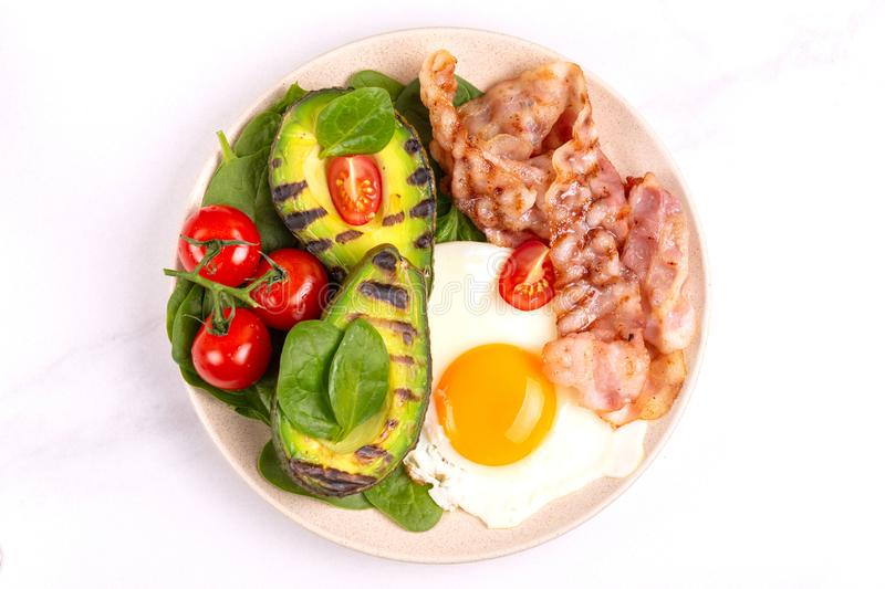 Ketogenic diet. Low carb high fat breakfast. Healthy food concept. Grilled bacon and avocado, fried eggs with spinach and cherry tomatoes on light marble stock image