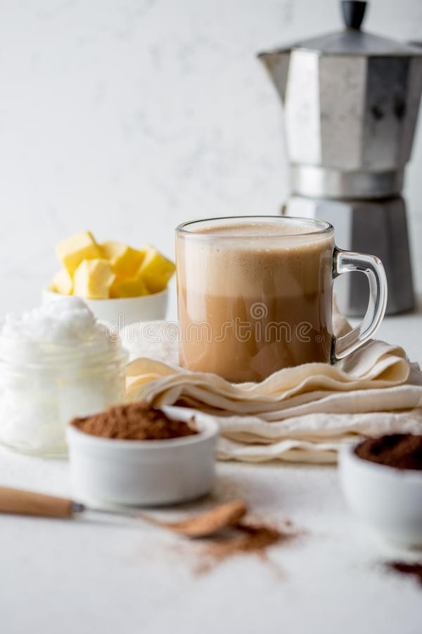 KETOGENIC KETO DIET DRINK. Coffe and cacao blended with coconut oil. Cup of bulletproof coffe with cacao and ingredients royalty free stock images