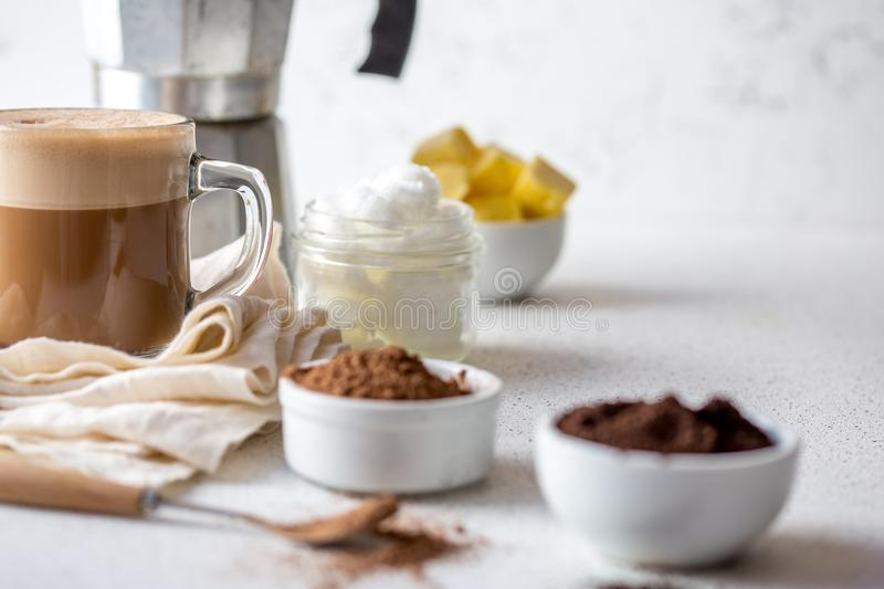 KETOGENIC KETO DIET DRINK. Coffe and cacao blended with coconut oil. Cup of bulletproof coffe with cacao and ingredients stock images