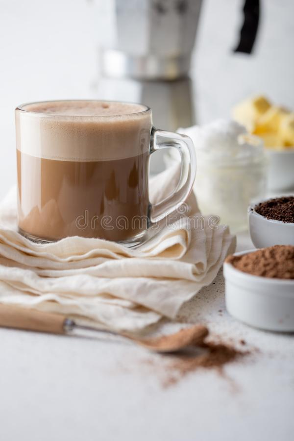 KETOGENIC KETO DIET DRINK. Coffe and cacao blended with coconut oil. Cup of bulletproof coffe with cacao and ingredients royalty free stock photography