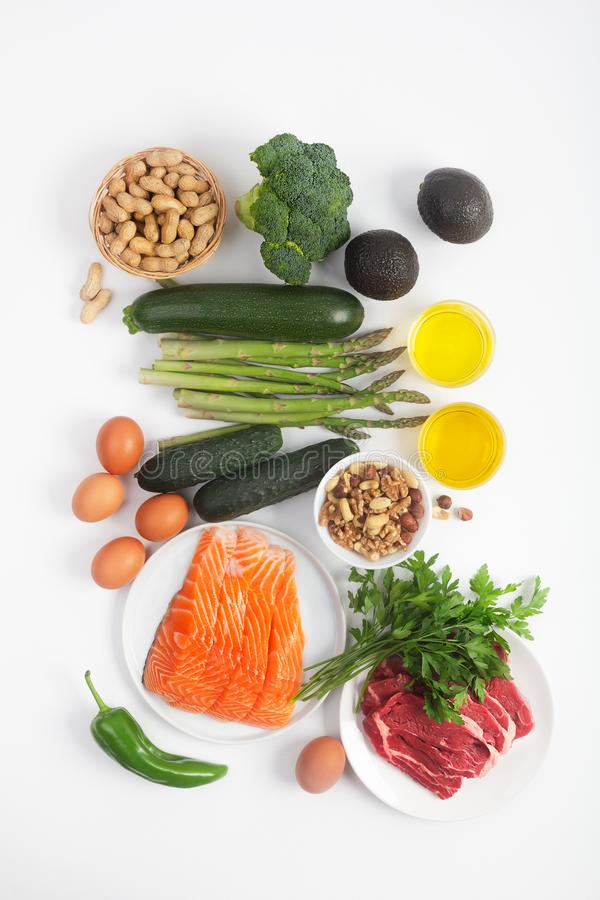 Ketogenic, keto diet, including vegetables, meat and fish, nuts and oil on white background. Ketogenic, keto diet, including vegetables, meat and fish, nuts and royalty free stock images