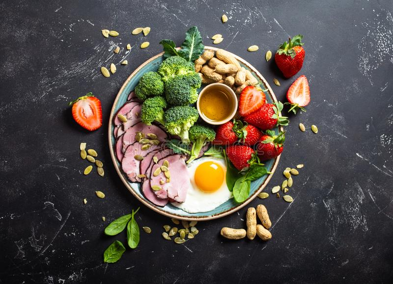 Keto diet concept. Ketogenic low carbs diet concept, top view. Plate on stone black background with keto foods: egg, meat, olive oil, broccoli, berries, nuts stock image