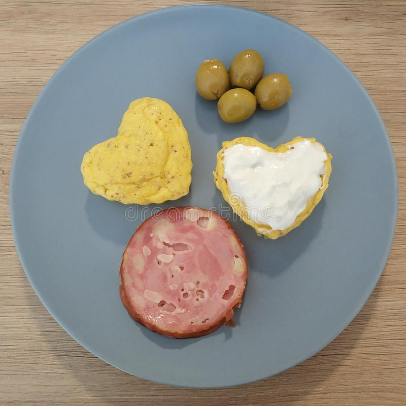 Ketogenic meal, heart bread, muffin with cream cheese, salami, olives. Keto food for weight loss. Healthy diet breakfast, dinner stock images