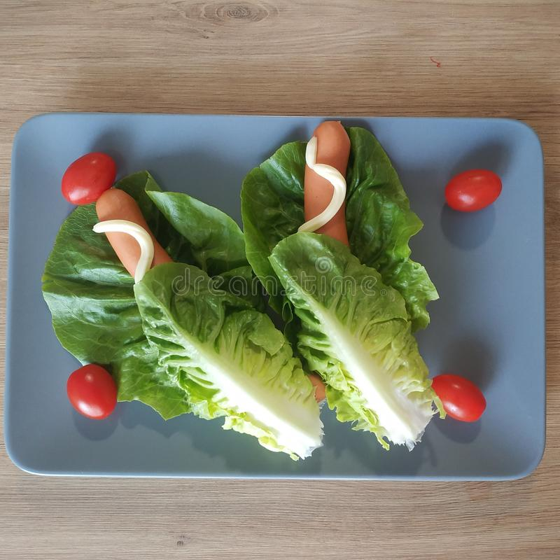 Ketogenic meal, lettuce wrapped hot dogs with tomatoes and mayonnaise. Keto food for weight loss. Healthy diet breakfast, dinner. stock photo