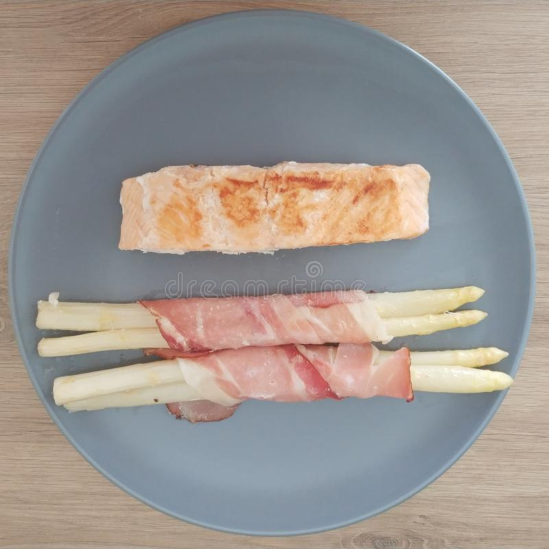 Ketogenic meal, salmon fish with bacon wrapped white asparagus. Keto food for weight loss. Healthy stock photo