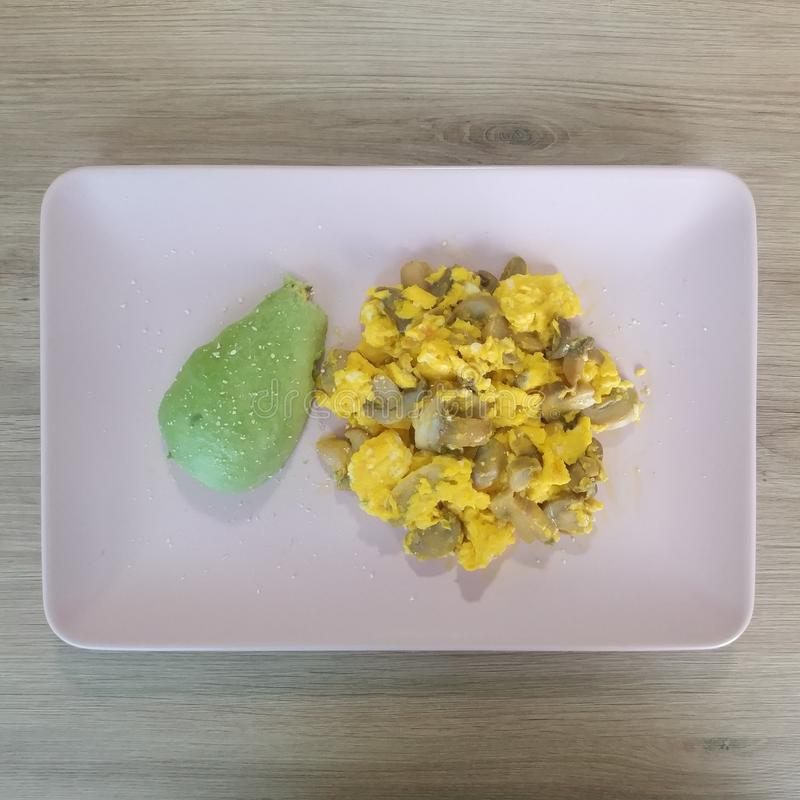 Ketogenic meal, scrambled eggs with avocado and mushrooms. Keto food for weight loss. Healthy diet dinner stock image