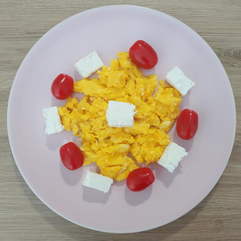 Ketogenic meal, scrambled eggs with feta cheese and tomatoes. Keto food for weight loss. Healthy diet breakfast or dinner. royalty free stock photo