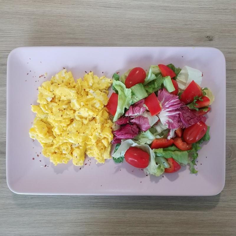 Ketogenic meal, scrambled eggs with tomatoes and lettuce mix. Keto food. Healthy, diet, breakfast, dinner royalty free stock photography