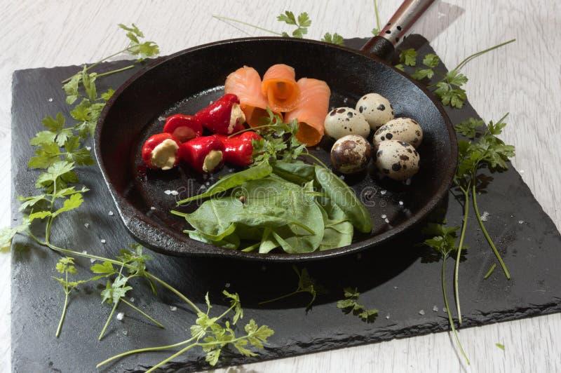 Ketogenic Nahrung in einer Gusseisenbratpfanne mit Frischkäsespinat der Wachtelei-Pepperonis und geräucherter Lachs auf einem Sch lizenzfreie stockfotografie