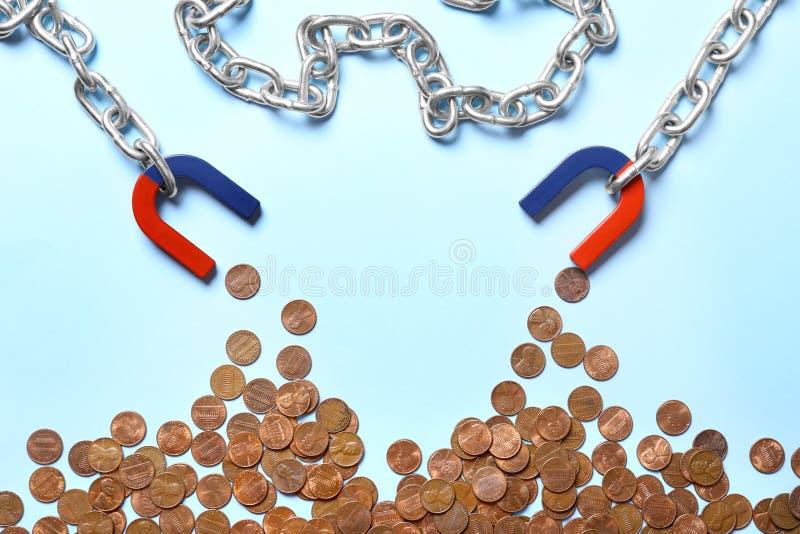 Kette mit Magneten, die Münzen auf blauem Hintergrund anziehen, flache Lagen lizenzfreie stockfotos