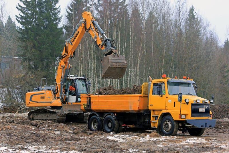 Kettenbagger Loads Sisu Tipper Truck lizenzfreie stockfotografie