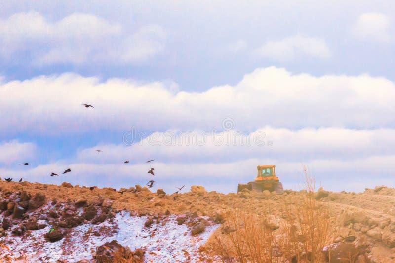 Kettenschlepper richtet das Gelände vor dem hintergrund der Wolken mit Fliegenvögeln aus lizenzfreie stockfotos