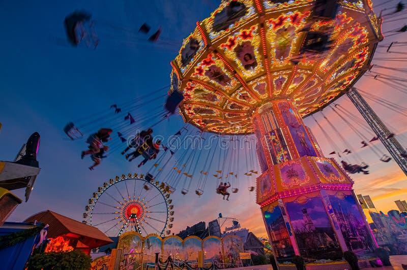 Ketting carusel met silhouttes van mensen die pret hebben in Oktoberfest in M?nchen royalty-vrije stock foto