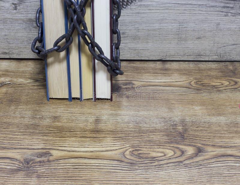 Ketting rond boeken op houten achtergrond wordt verpakt die royalty-vrije stock foto
