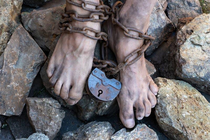 Kettingen met een slot op de benen van een slaaf in het midden van stenen Kettingen bij de enkel Het symbool van de slavernij royalty-vrije stock afbeeldingen
