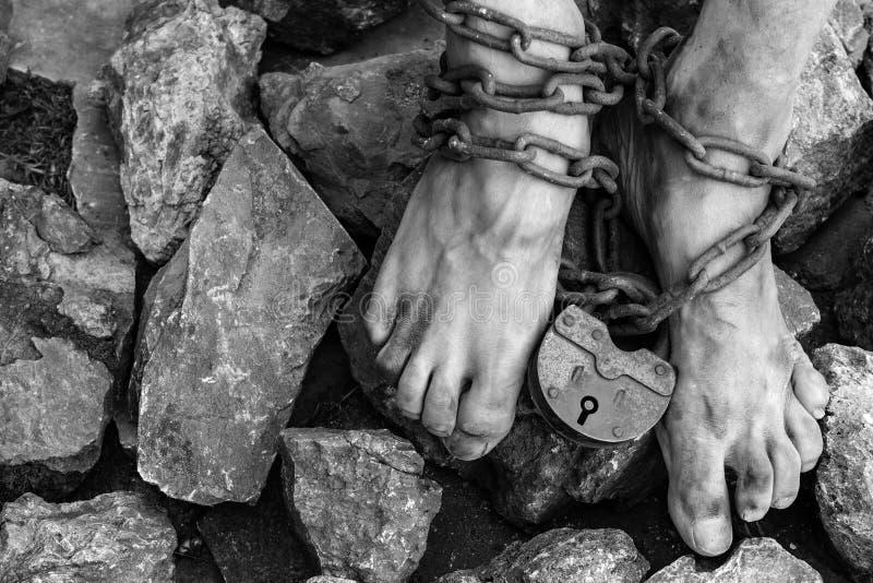 Kettingen met een slot op de benen van een slaaf in het midden van stenen Kettingen bij de enkel Het symbool van de slavernij royalty-vrije stock afbeelding