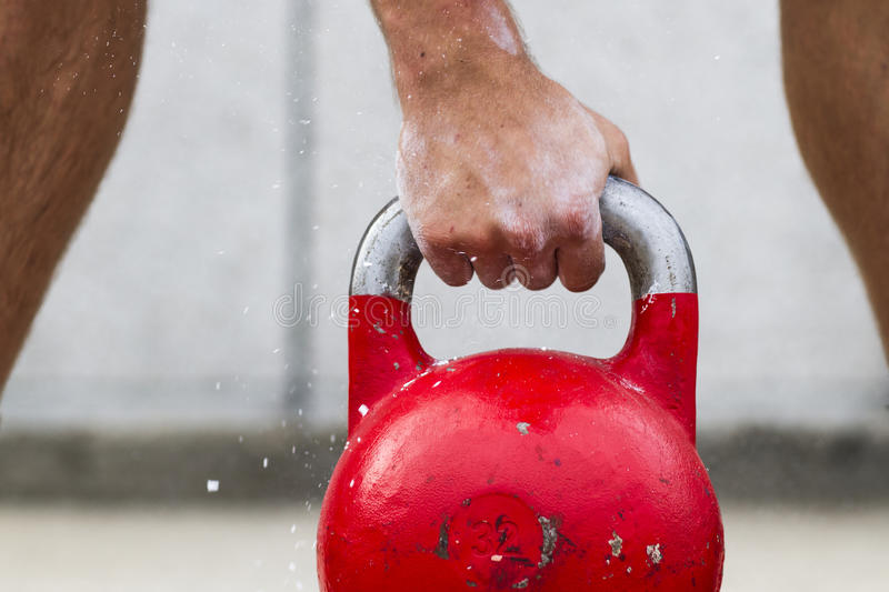 Kettle bell. Man picking up a kettle bell used for crossfit stock image